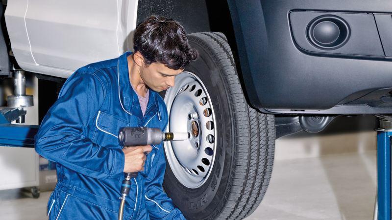Ein Mechaniker zieht die Schrauben an einem montierten Reifen fest.