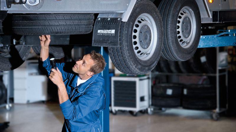 Ein Mechaniker prüft den Ersatzreifen an einem Fahrzeug.