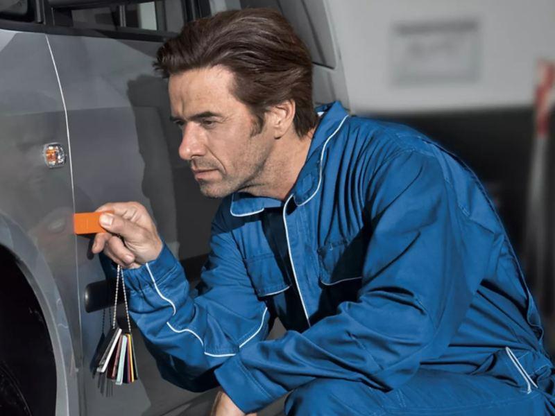 Ein Mechaniker überprüft die Tür eines Autos.