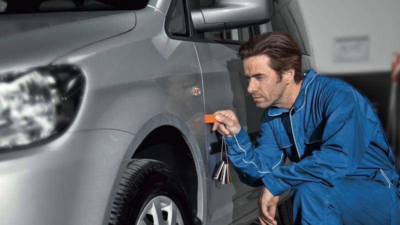 Ein Mechaniker überprüft Spaltmaße an einem Fahrzeug.