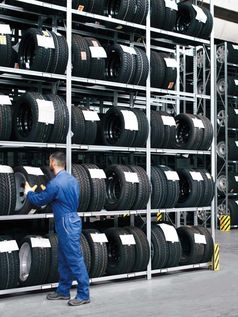 Ein Mechaniker nimmt einen Reifen aus dem Reifenlager.