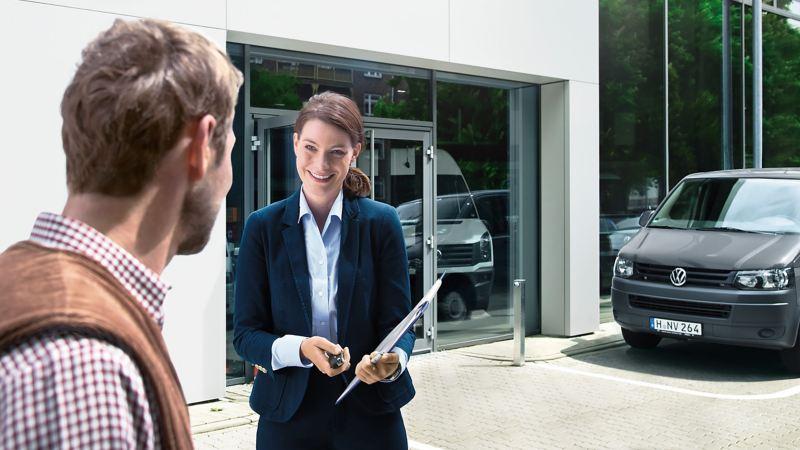 Eine Frau übergibt Wagenschlüssel an einen männlichen Kunden