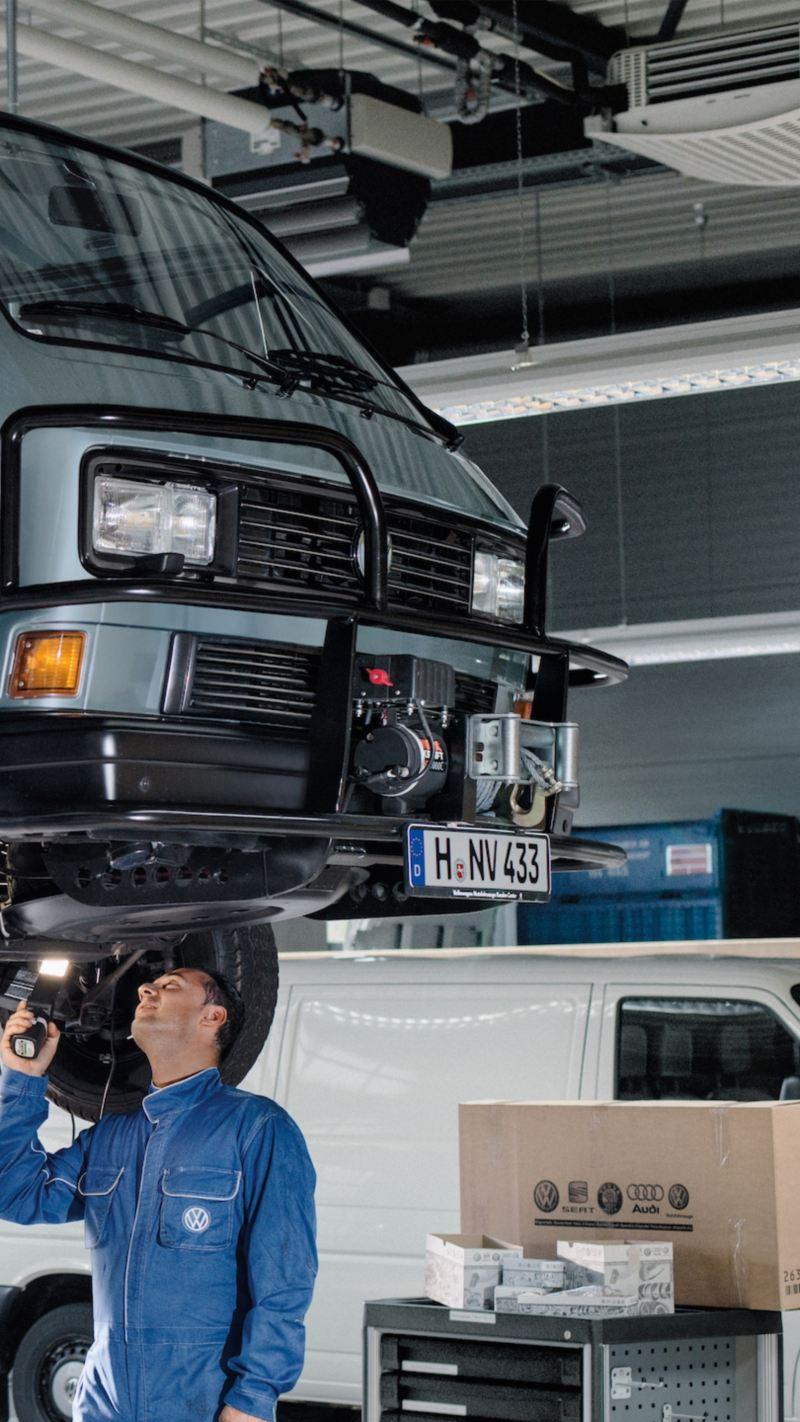 Mechanik dokonuje inspekcji podwozia pojazdu Volkswagen T3 Transporter.