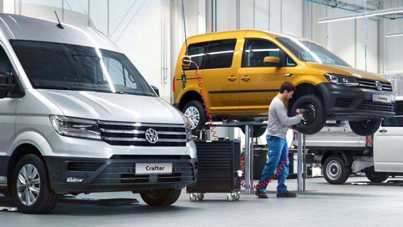 Un addetto Volkswagen Service intento a cambiare la gomma di un Caddy.