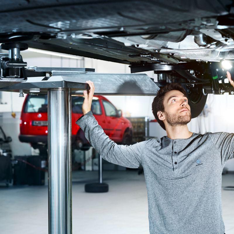 Pracownik serwisu dokonuje inspekcji podwozia pojazdu.