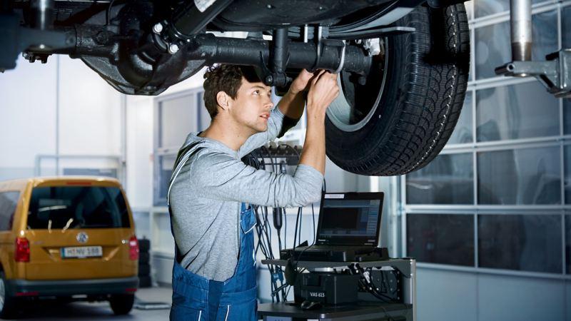 Ein Mechaniker überprüft den Unterboden eines Fahrzeugs, das auf einer Hebebühne steht