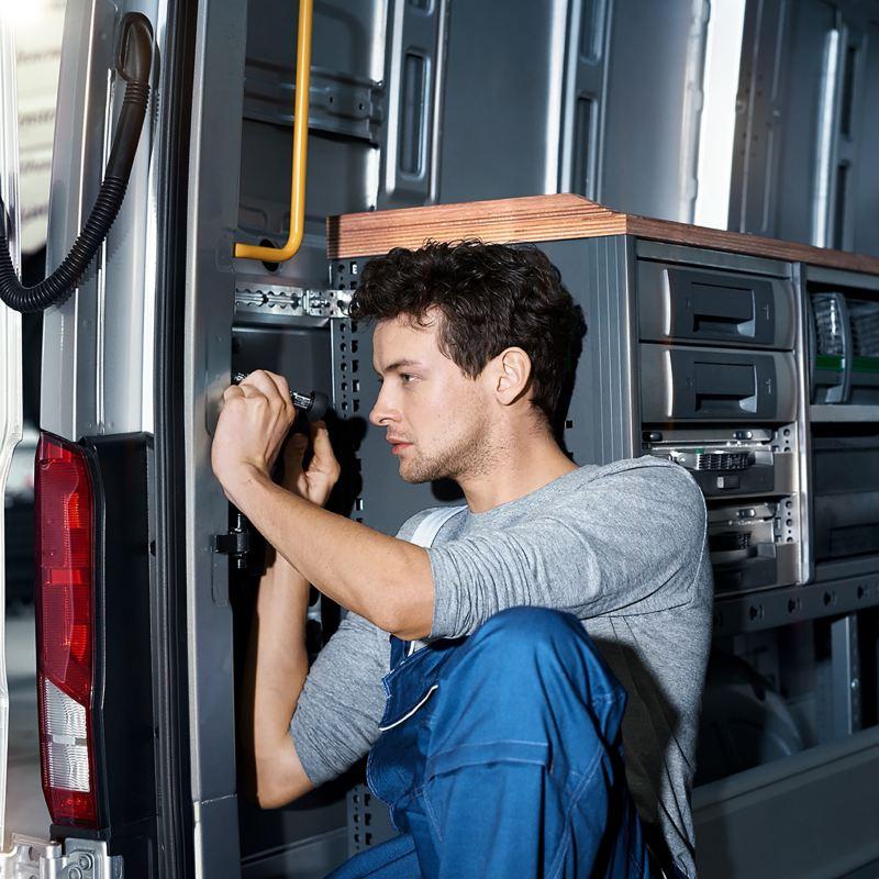 Ein Mechaniker überprüft das Schoss am Heck einen Fahrzeugs.