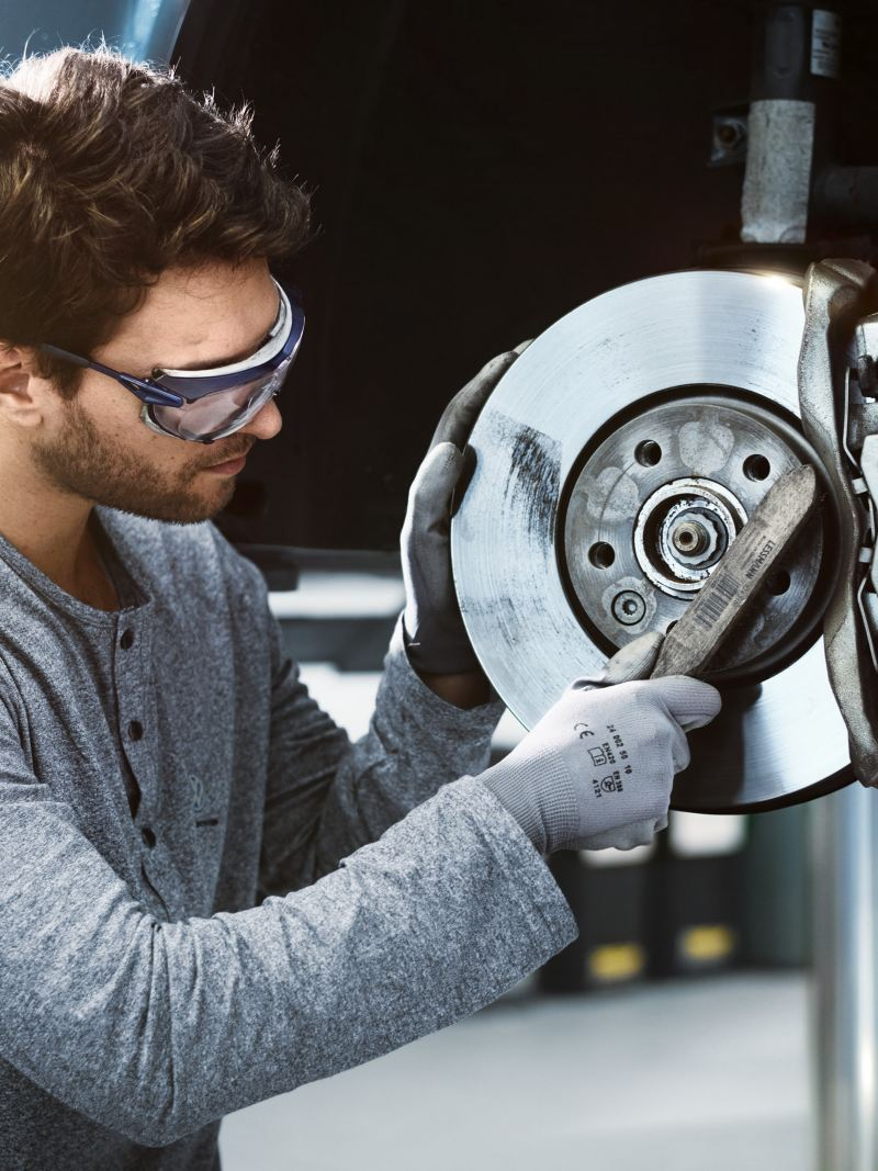 Ein Mechaniker checkt die Bremsen eines Volkswagen Nutzfahrzeuges.