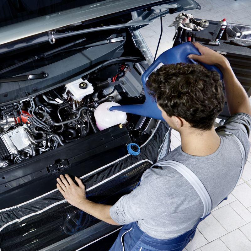 Pracownik serwisu przy otwartej komorze silnika.