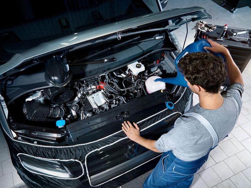 Ein Mechaniker füllt Scheibenklar nach.