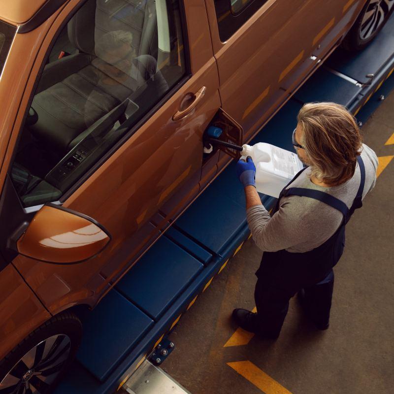 Ein Volkswagen Service Partner füllt Kühlflüssigkeit nach.