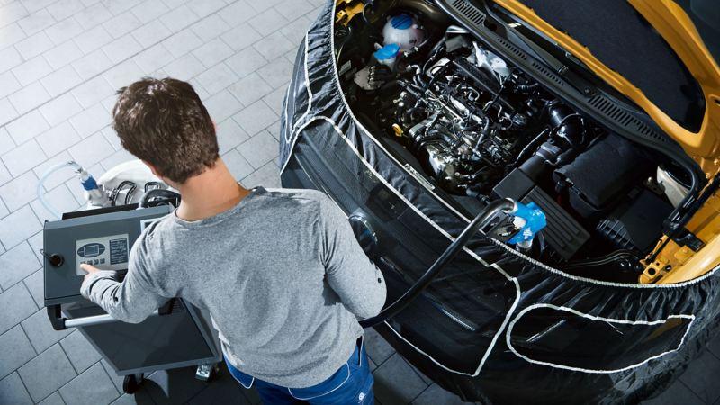 Mekaniker fyller på med AdBlue-vätska i en Volkswagen transportbil