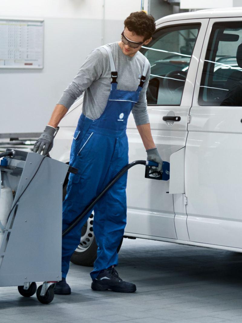 Ein Mechaniker füllt AdBlue an einem Fahrzeug nach.