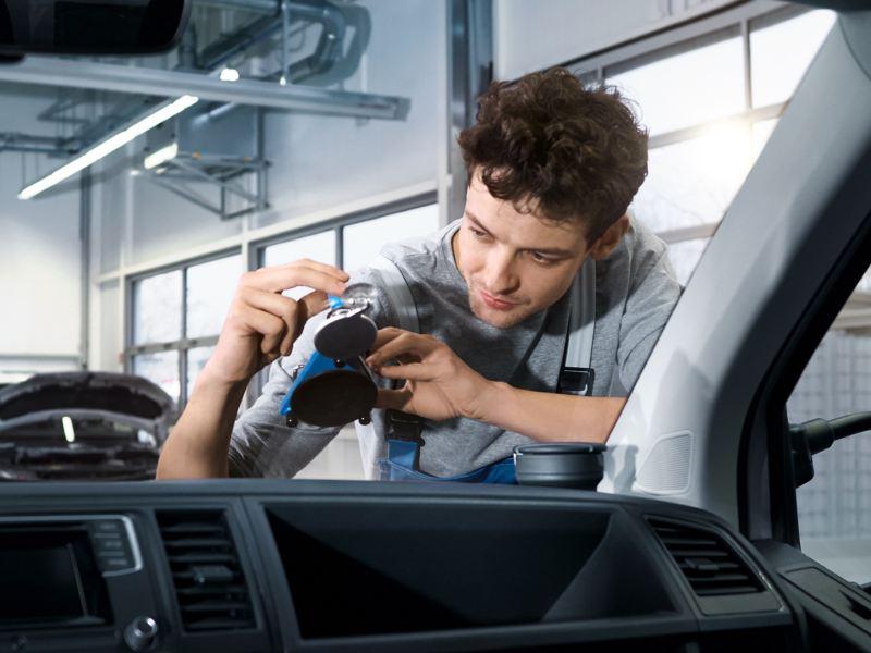 Ein Service Plus Mechaniker repariert die Windschutzscheibe eines Volkswagen Nutzfahrzeuges.