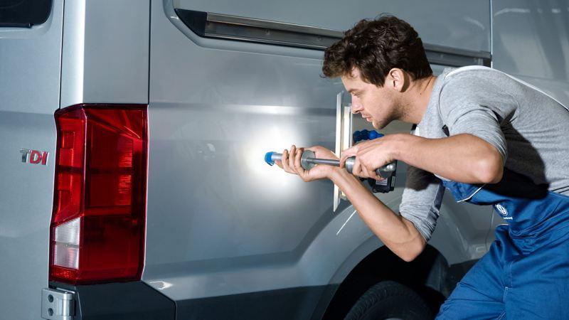 Ein Mechaniker prüft die Lackstärke an einem Fahrzeug.