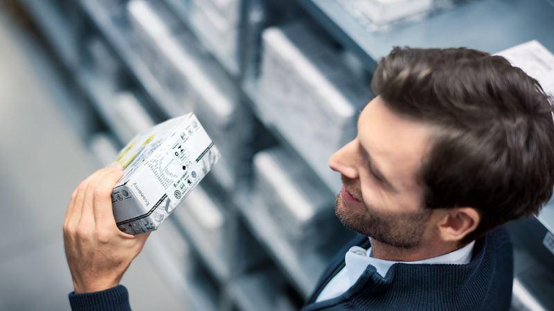 Ein Mann prüft den Aufdruck einer Verpackung.