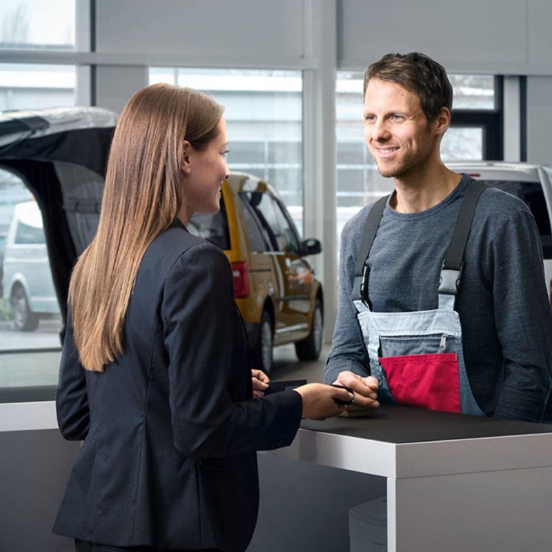 Ein Mann spricht mit einer Frau in einem Autohaus über einen Tresen hinweg.