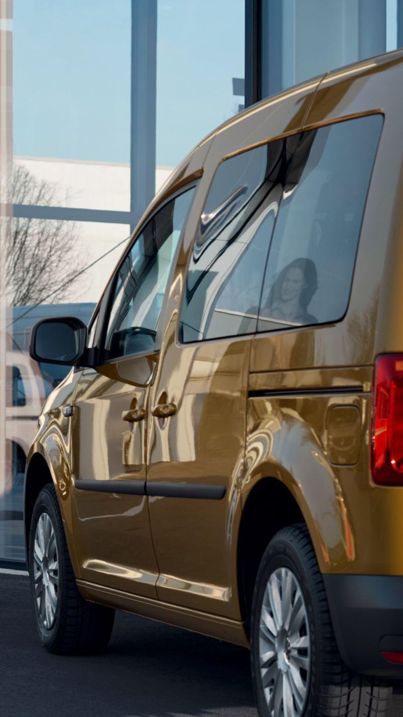 Volkswagen Caddy zaparkowany przed salonem Volkswagen Samochody Dostawcze.