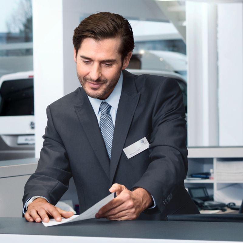 Ein Mann im Anzugs sitzt auf ein Papier verweisend am Tisch