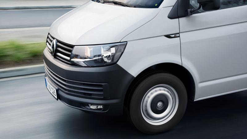 Biały Volkswagen Transporter na drodze.