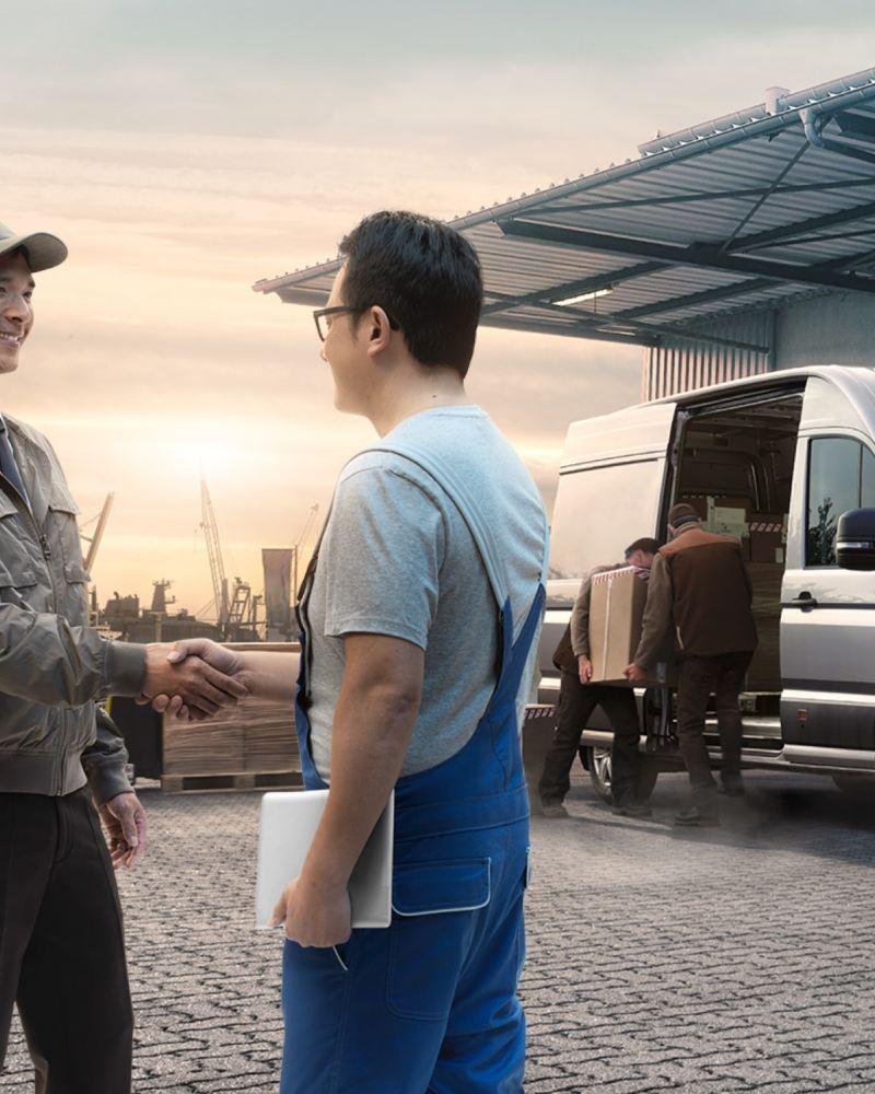 Ein Mann schüttelt die Hand von einem Mechaniker in der Garage von einer Autohauswerkstatt