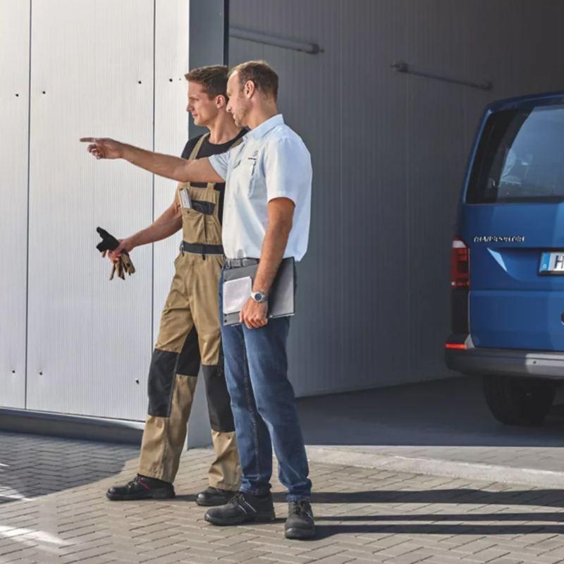 Zwei Männer stehen vor einer Garage. Einer zeigt auf etwas links außerhalb des Bildes.