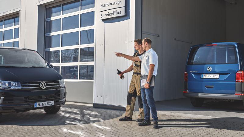 Dwóch mężczyzn rozmawia między dwoma furgonami Volkswagen.