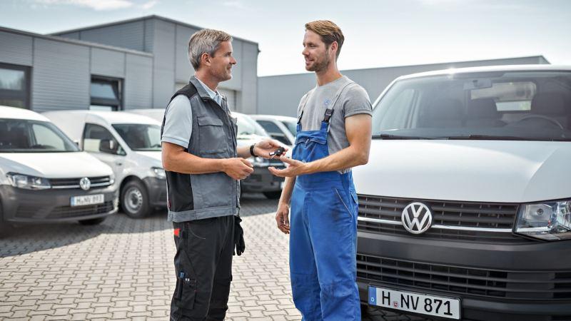 Zwei Männer unterhalten sich während einer Schlüsselübergabe für ein Fahrzeug.