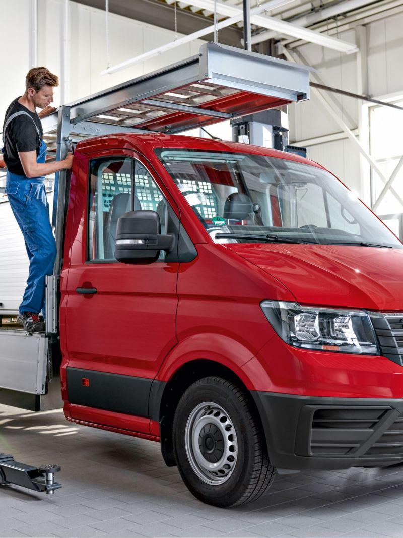 Mechanik montuje drabinę do Volkswagen Crafter Skrzyniowy.