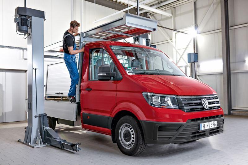 EIn Mechaniker befestigt eine Leiter auf einem Crafter Pritschenwagen.