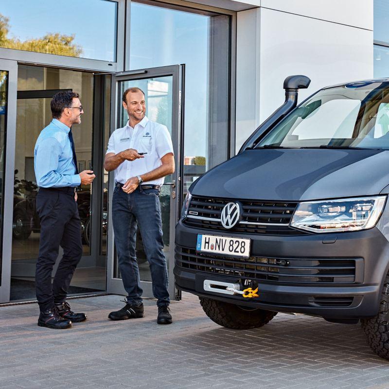 Zwei Männer unterhalten sich neben einem VW-Transporter.