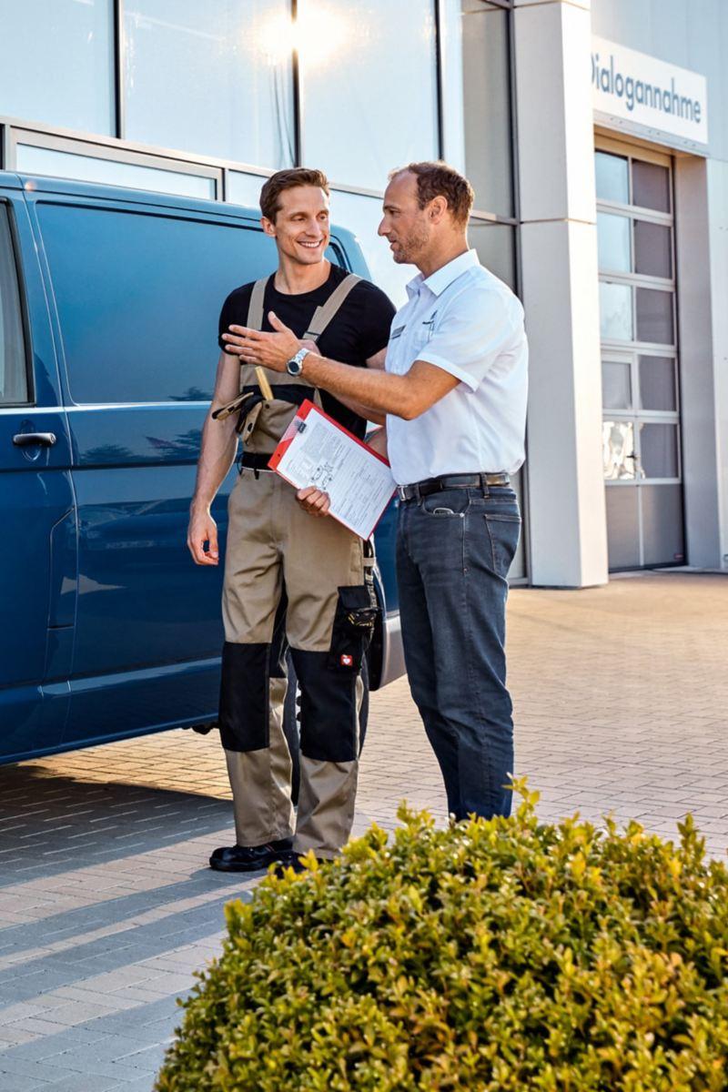 Dwóch mężczyzn rozmawia obok Volkswagen Transporter Furgon.