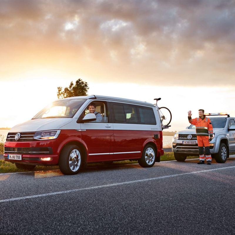Ein Multivan und ein Amarok auf einer Landstraße, daneben stehen zwei Männer.