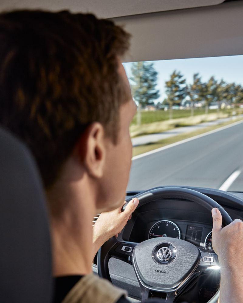 Ein Mann am Steuer eines Volkswagen Transporters fährt über eine Landstraße.