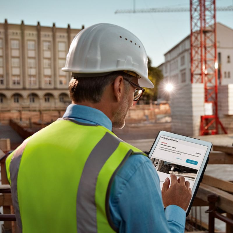Bauarbeiter schaut auf einer Baustelle auf sein Tablet