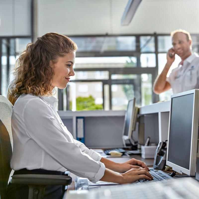 Eine Frau sitzt an einem Rechner und tippt.