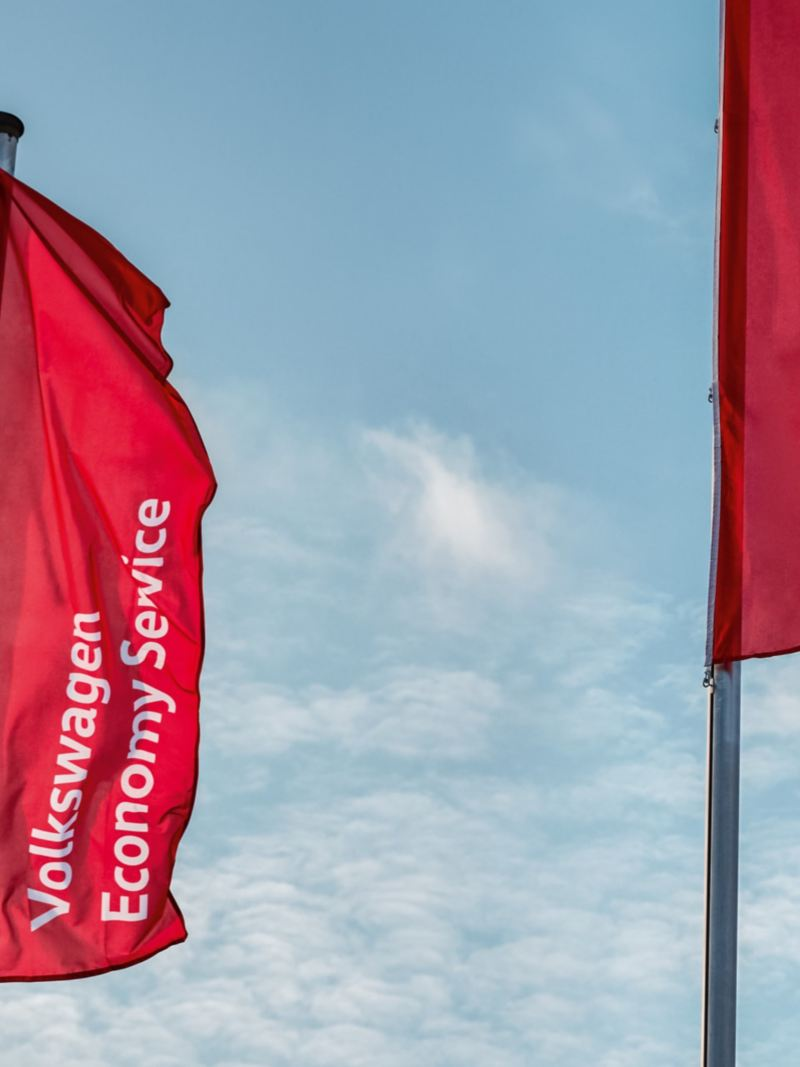 Im Wind wehende Fahnen mit dem Schriftzug des Volkswagen Economy Service.