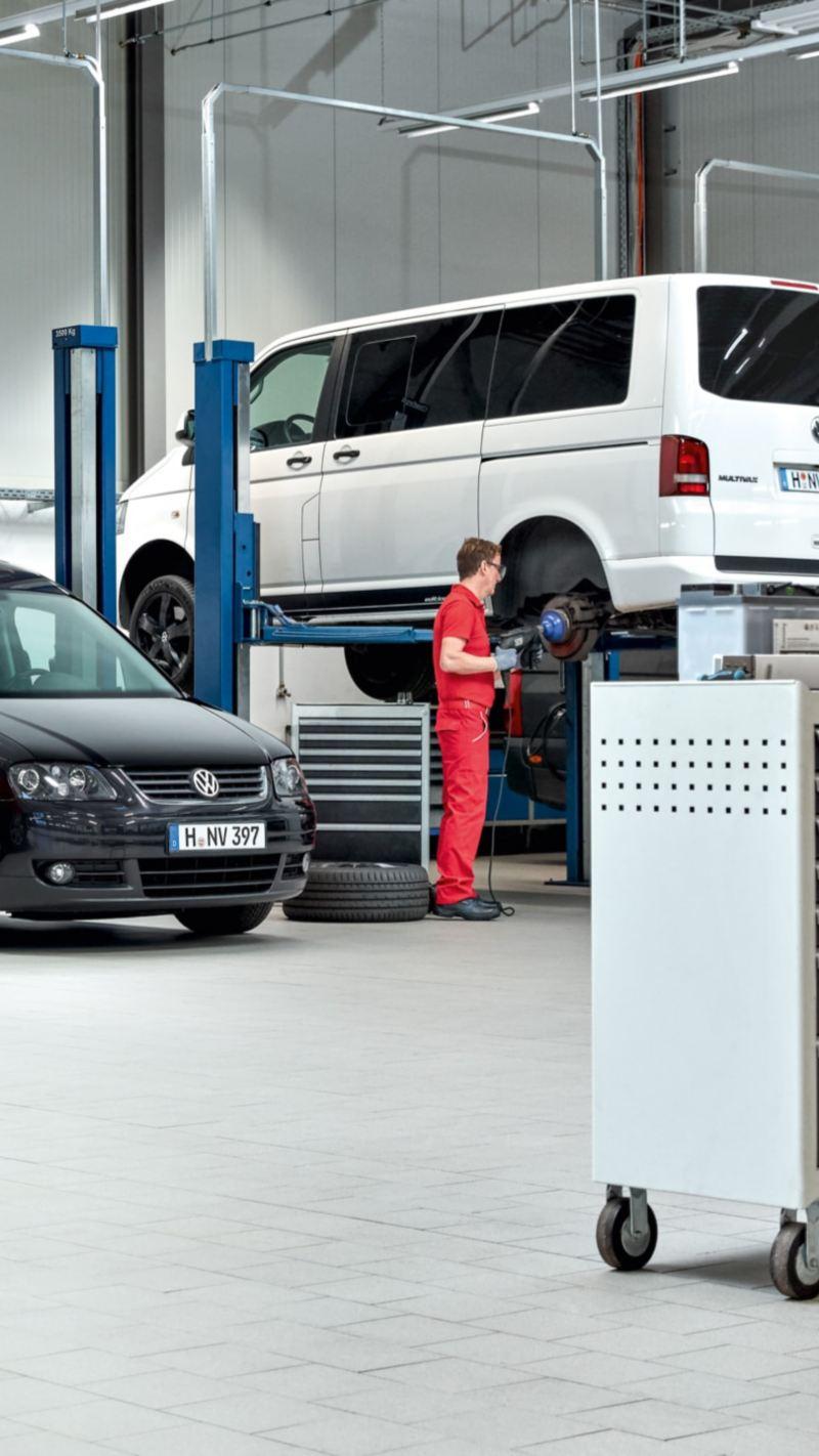 Ein Mechaniker schiebt einen Werkzeugwagen durch eine Werkshalle von Volkswagen Nutzfahrzeuge.