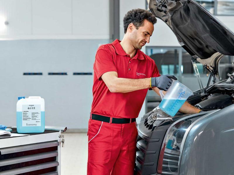 Ein Service Partner füllt Scheibenreinigungsmittel nach.