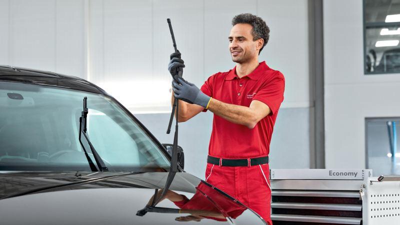 Ein Mechaniker prüft die Wischerblätter an einem Fahrzeug.