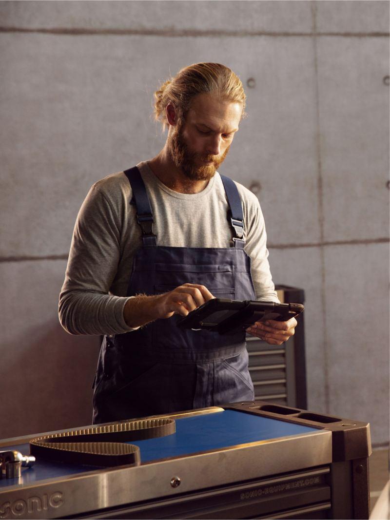 Ein Mechaniker steht neben einem geöffneten Motorraum mit einem Klemmbrett in der Hand.