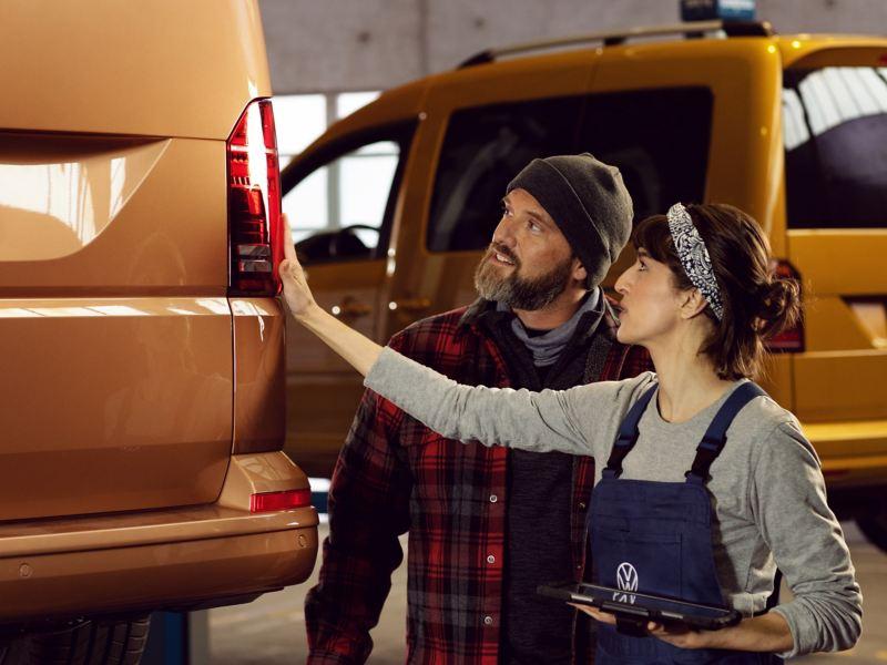 Eine Mechanikerin zeigt dem Kunden die Servicearbeiten an seinem Volkswagen Nutzfahrzeug-