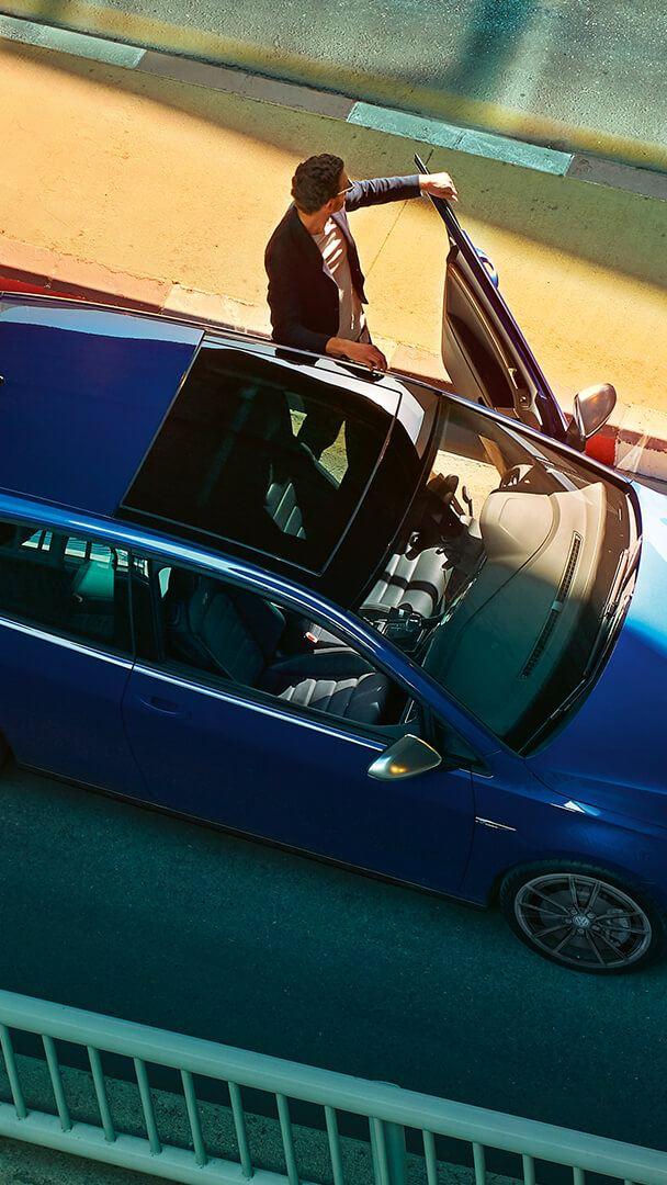 Un homme observe les lieux en tenant la portière de sa Volkswagen