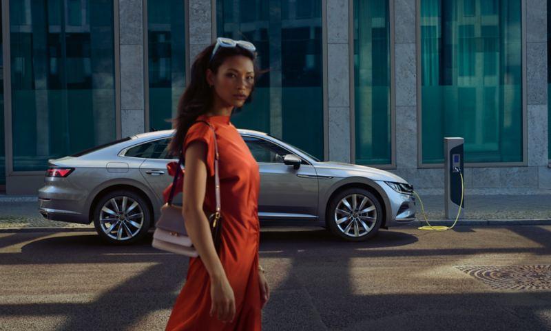 Arteon eHybrid in Silber steht seitlich an der Straße angeschlossen an Ladekabel. Eine junge, moderne Frau geht vorbei.