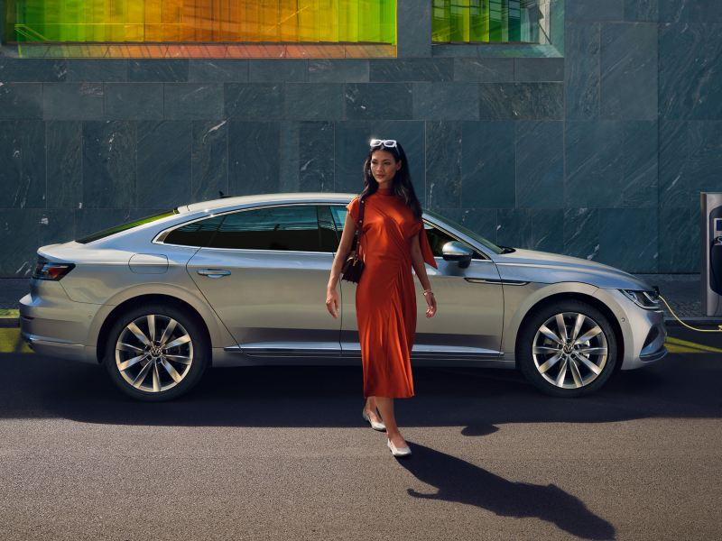 VW Arteon eHybrid in Silber lädt an Tanksäule. Frau geht vorbei.