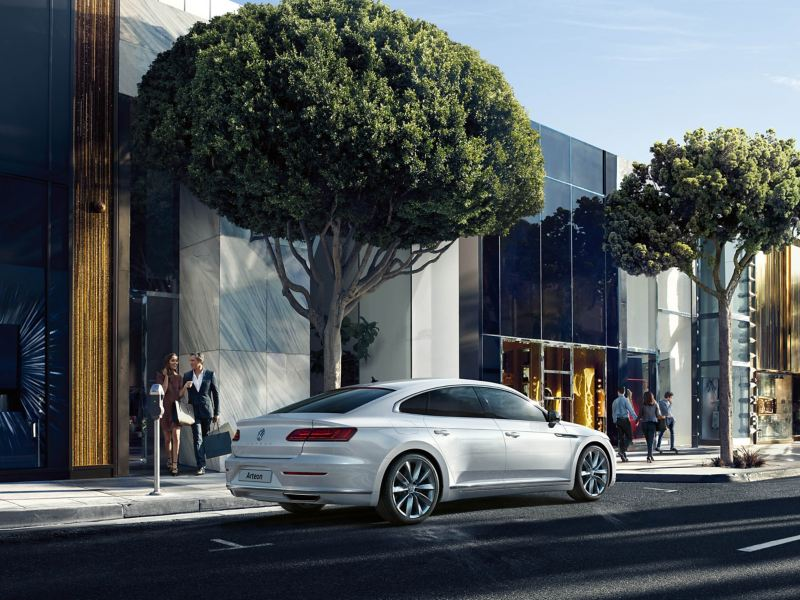 A white Volkswagen Arteon parked on a city street outside of shops, with pedestrians shopping.