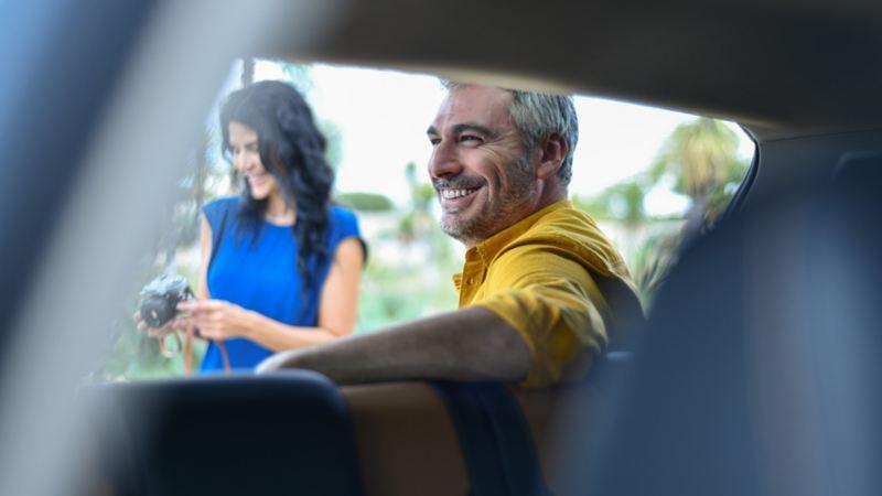 Padre recargado en auto después de servicio de mantenimiento especializado regalado por día del Padre