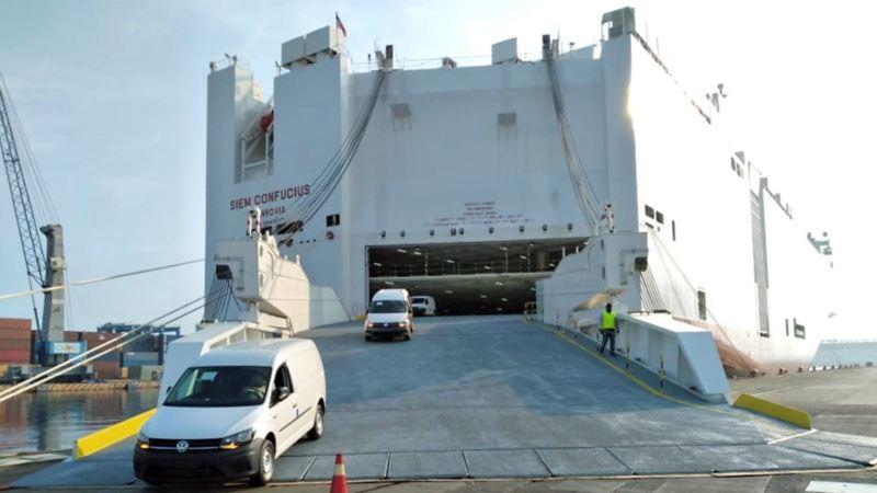 Automóviles bajando de SIEM CONFUCIUS, el buque que transporta modelos de autos Volkswagen