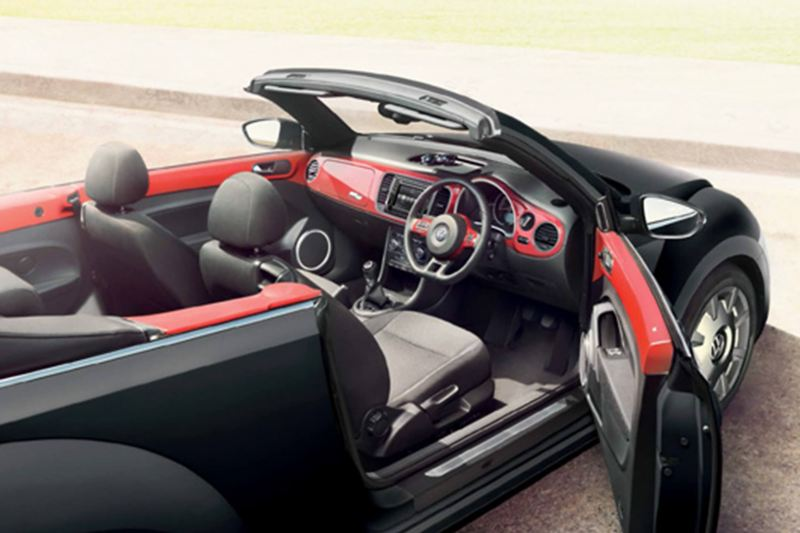 Interior shot of a red Volkswagen Beetle Cabriolet, next to the beach with the roof down and the drivers door open.