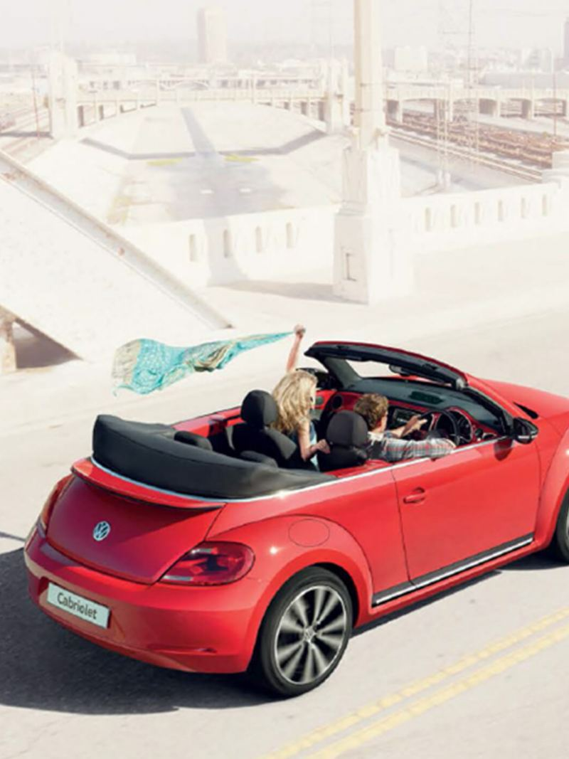 A couple driving a red Volkswagen Beetle Cabriolet, the roof down next to an old city.